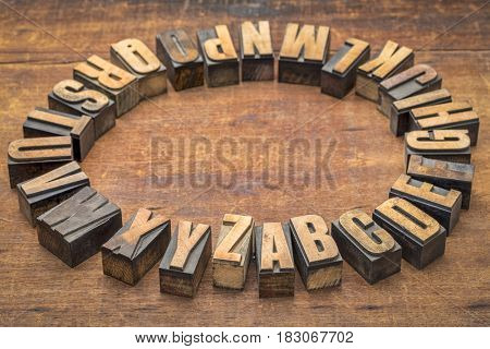 alphabet circle in vintage letterpress wood type against grunge wooden board
