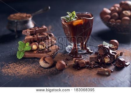 Homemade hazelnut spread or hot chocolate in glass bowl with nuts and chocolate bar. Ingredients for cooking homemade chocolate sweets. Confectionery and sweets concept.