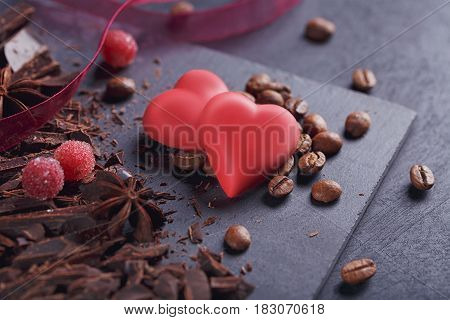 Dark chopping chocolate black roasted coffee beans red berries red chocolate with heart shape anise spice on slate board over black textural background. Confectionery and sweets concept