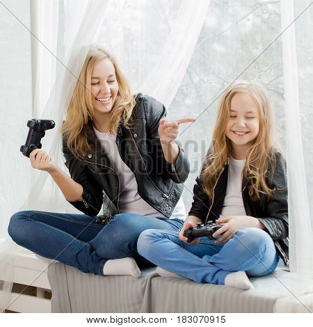 Family games. Mother and daughter play on conlsole together