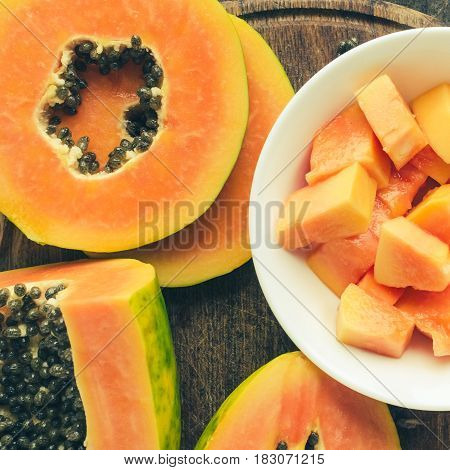 Slices of ripe sweet papaya in white bowl on old wooden background. Top view. Square.