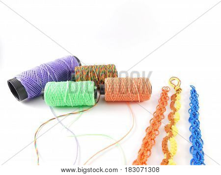 Yarns of different colors and bracelets made by hand.
