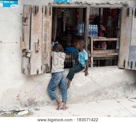Zanzibar, Tanzania - July 14, 2016: Local children in Zanzibar, Tanzania, playing near a failed store with heavy shutters