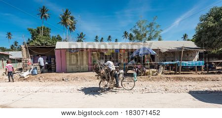 Zanzibar, Tanzania - July 14, 2016: Man carrying wood and trash on his bicycle, old half-ruined shack on background, Zanzibar, Tanzania