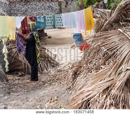 Zanzibar, Tanzania - July 14, 2016: Muslim woman in burka hangning clothing near her shack, Zanzibar, Tanzania