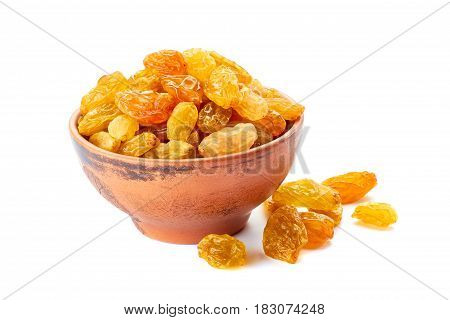 Ceramic bowl and heap with golden raisins isolated on white background