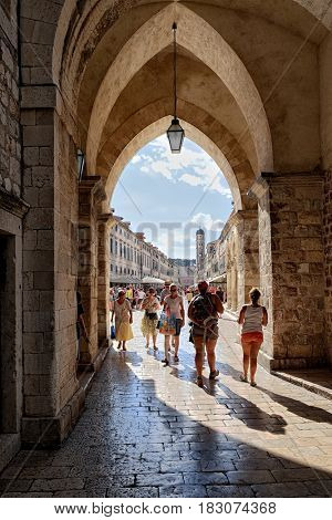 DUBROVNIK OLD TOWN, CROATIA - JULY 20, 2016: Stradun or Placa main street crowded of tourists from gothic arches of Clocktower, on background bell tower of Franciscan Monastery