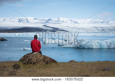 Man traveler in red jacket sits on the shore of a lake. Summer landscape with glacial lagoon, glacier and icebergs in the southeast of Iceland, Europe, near the national park Vatnajokull