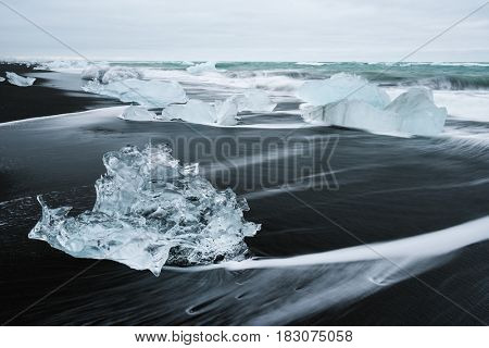 Icy beach in Iceland, Europe. Ice on the black volcanic sand on the Atlantic Ocean. Tourist attraction. Amazing landscape cloudy day