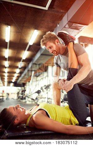 Trainer help girl in exercises in gym