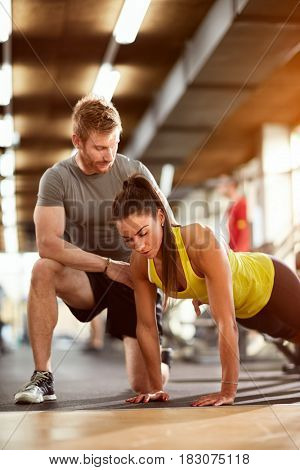 Woman doing pushups with man's assist in fitness club