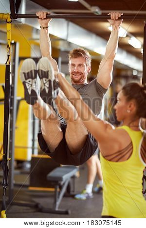 Man with female instructor in gym on exercise equipment