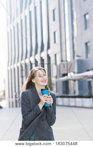 Beautiful blond woman in a blue coat on the background of a business center. A woman is posing in the middle of the street. The woman is holding a thermo mug in her hands. Girl drinking coffee