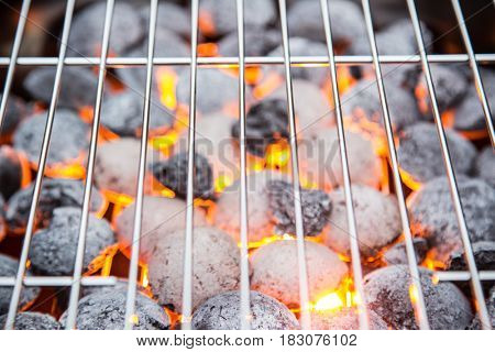 Garden grill with blistering briquettes, close-up.