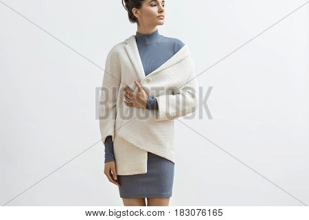 Elegance girl is posing in the studio on the light background. She wears a gray dress and a white coat. Woman holds left hand on the hip, right hand on her chest and looks to the side. Horizontal.