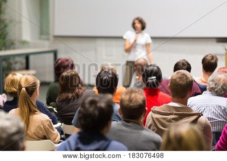 Female speaker giving presentation in lecture hall at university workshop. Audience in the conference hall. Rear view of unrecognized participant in audience. Scientific conference event.