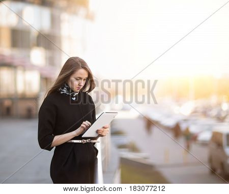 Successful business woman working on a digital tablet near an office building. The photo has empty space for text