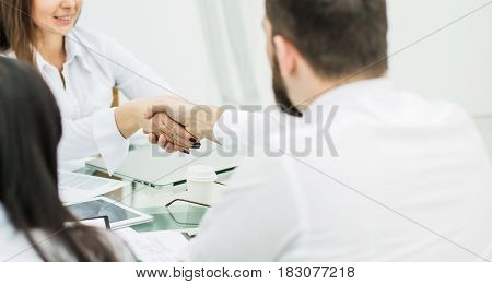 closeup of a handshake between the Manager and the client after the signing of the financial agreement in the workplace in the office