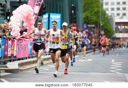 London, UK - April 23, 2017: London Marathon. Professional sprinters arriving the first in Canary Wharf. People cheering the sportsmen.