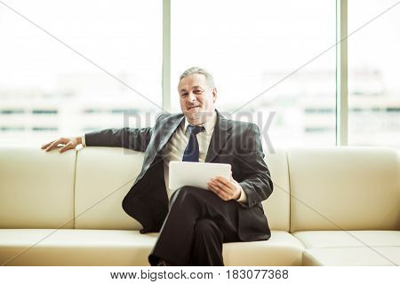 businessman looking at the screen of a digital tablet sitting on sofa in modern office