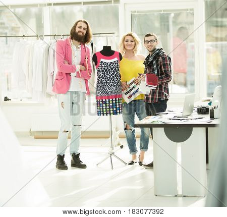 group for fashion designers in Studio on a background of new models of clothes