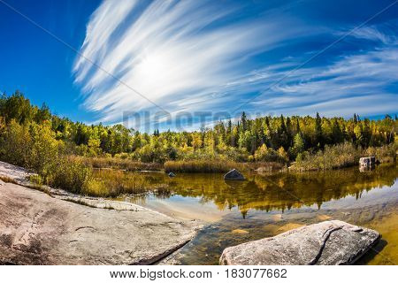Indian summer in Manitoba, Canada. Incredible cirrus clouds over the Winnipeg River. Old Pinawa Dam Park. The concept of ecological and recreational tourism