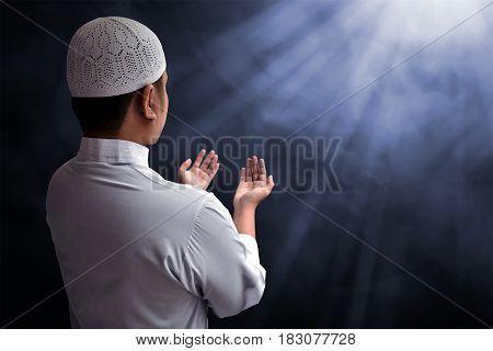 Muslim man praying to God with smoke background