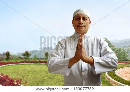Old muslim man smiling and greeting at garden