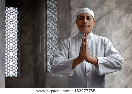 Old muslim man smiling and greeting in mosque