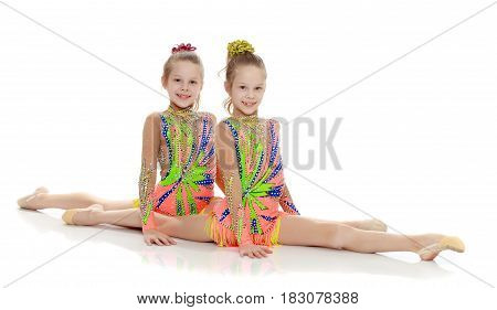 Two adorable little twin girls, gymnastics in the sports school. Girls beautiful gymnastic leotards. They do the splits.Isolated on white background.