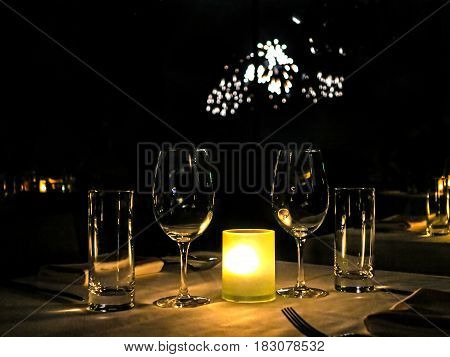 Some glasses on a table with fireworks behind