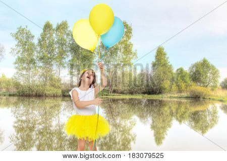 Pretty little blonde girl in a short bright yellow skirt and white blouse.Girl holds in hands balloons , She looks at them from the bottom up.