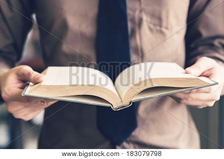 Business Man Hand Holding Book And Reading At Window.