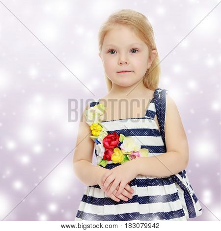 The little blonde girl in striped summer dress with beach bag on shoulder.