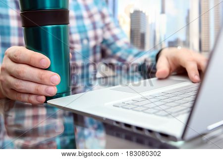 Business man working and analyzing financial figures on a graphs using laptop. Cup of tee or cofee near.