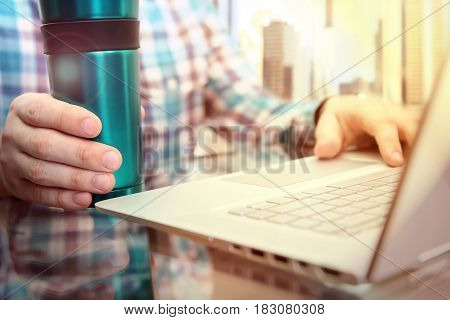 business man working and analyzing financial figures using laptop in the office with cofee or tee