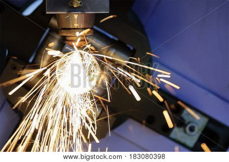 The CNC laser cut machine while cutting the steel tube with the sparking light.The hi-precision tube cutting process by laser cut