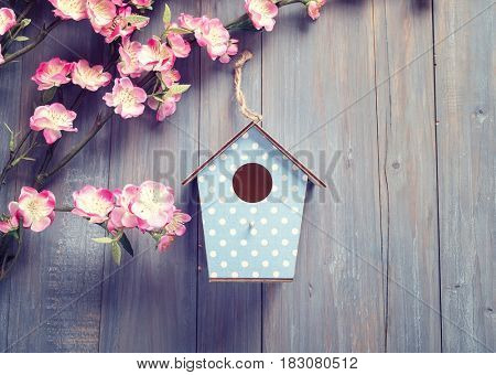 birdhouse hang on spring tree flowers with antique rustic wood background.
