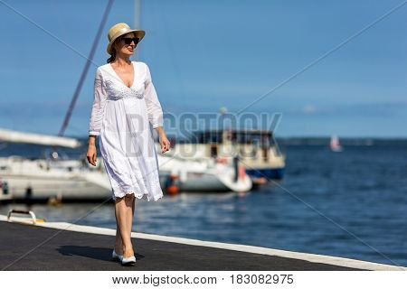 Middle-aged woman on vacation walking in marina
