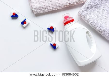 Bath towels stack with detergent plastic bottle in laundry on light table background top view mockup