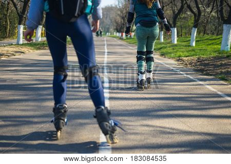 Competitions in roller skating.Two girls on roller skates ride along the road. The second girl is tired and stopping.