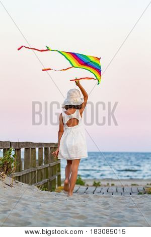 Girl with rainbow colorful kite on the beach at sunset