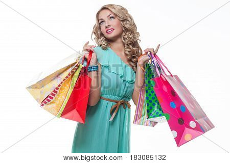 Beautiful happy blond young woman holding many colorful shopping paper bags. Isolated on white background. Copy space.