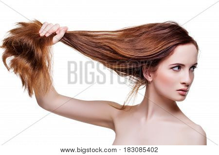 Beautiful young woman pulling her long red brown natural hair. Beauty shot isolate on white background. Copy space.