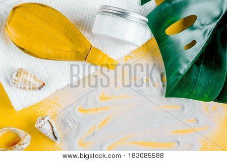 Woman cosmetic set with sun protection lotion for summer seaside rest on orange desk background top view mock-up