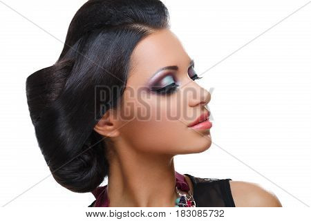 Beautiful young woman with bright purple and green make-up and fancy hairdo. Beauty shot isolated on white background. Copy space.