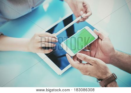 Man showing smartphone to woman while they discussing a project. Clipping path included.