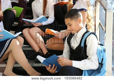 Happy pupils with books sitting on school stairs