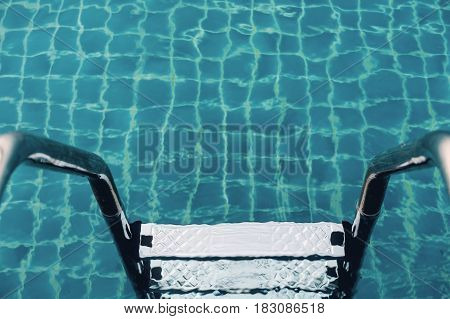 Pool ladders in swimming pool, summer water recreation concept