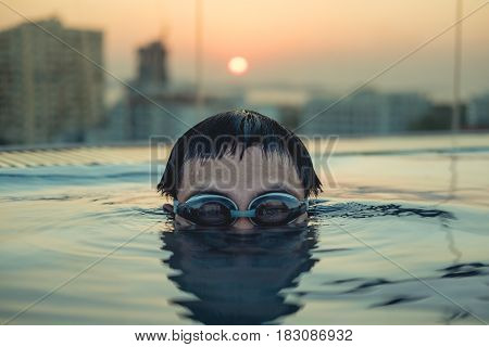 Close-up young man head shot in swimming pool in summer sunset
